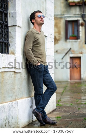 Young caucasian man standing on street - stock photo