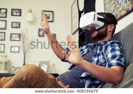 Young Caucasian man trying to push something using white virtual reality headset glasses - stock photo