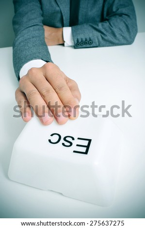 young caucasian man wearing a gray suit sitting at his office desk pressing a giant escape key with his hand - stock photo