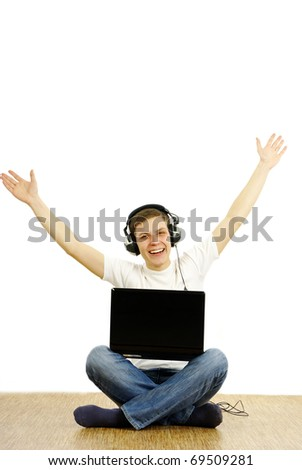Young caucasian man with headphones and laptop, sitting cross-legged and listening music. Studio shot. White background. - stock photo