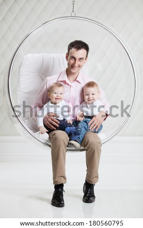 Young Caucasian man with two babies having fun while sitting in swinging hanging chair - stock photo