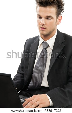 Young Caucasian man working on laptop indoors over white background. - stock photo