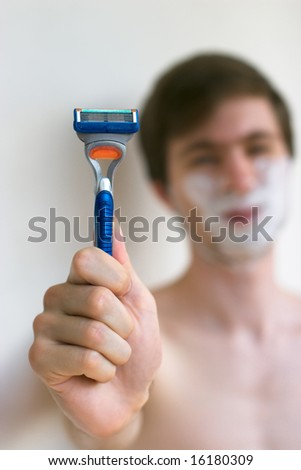 Young caucasian men holding a razor in hand in front of unfocused face - stock photo