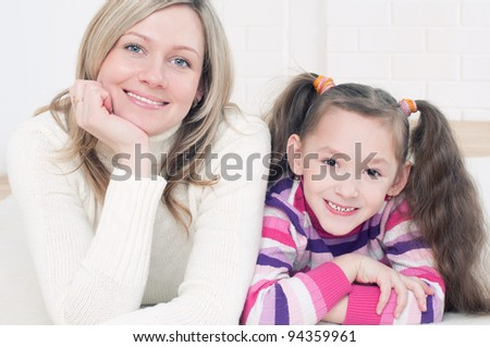 Young caucasian mom and her little girl lying on the floor and smiling - stock photo