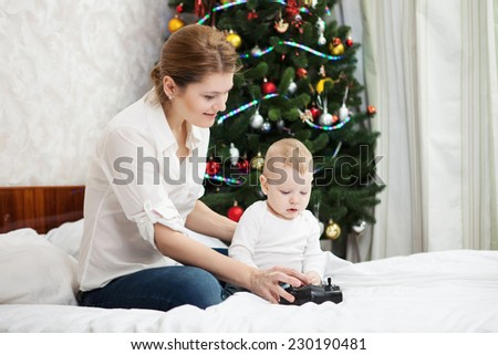 Young Caucasian mother and toddler son playing with RC controller against decorated Christmas tree at home - stock photo