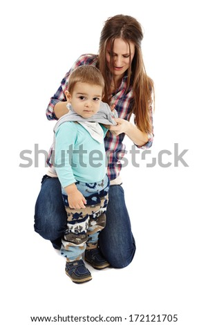Young caucasian mother dressing up her little boy, isolated on white background