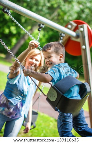 Young caucasian mother with swinging son at playground, teeth smile