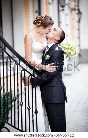 Young caucasian newly married couple having a long kiss outdoor - stock photo
