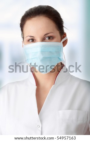 Young caucasian nurse in mask - stock photo