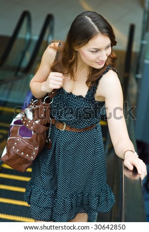 young caucasian on escalator in shopping mall - stock photo