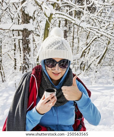Young caucasian positive woman drinking hot tea in winter nature. - stock photo