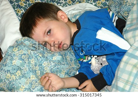 young caucasian preschool age boy laying on pillows looking ill, not feeling good, not happy, sad - stock photo