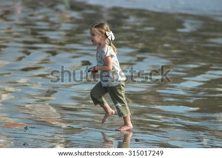 Young caucasian preschool age girl running on a wet sandy beach with water reflecting off the wet sand - stock photo