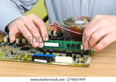 Young caucasian repairman working in computer store, repairing computer and adding ram to pc. Focus on RAM memory, - stock photo