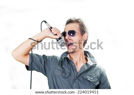 Young caucasian rock singer wearing sunglasses on the white background - stock photo