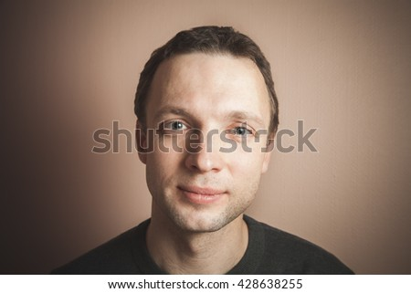 Young Caucasian smiling man, close up studio portrait over gray wall background, vintage stylized photo filter, retro tonal correction effect - stock photo