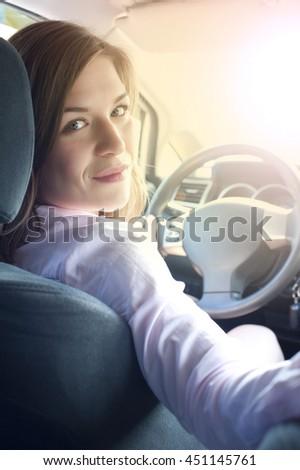 Young caucasian smiling woman in car holding steering wheel - stock photo