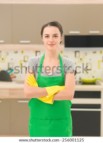 young caucasian smiling woman wearing apron and rubber gloves, standing in kitchen - stock photo