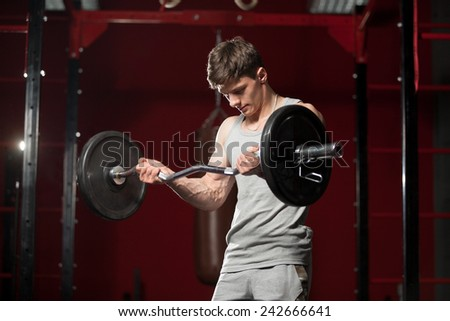 Young caucasian sportsman lifts barbell in fitness center - stock photo
