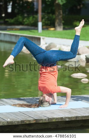 Young caucasian sporty woman making shirshasana outdoors