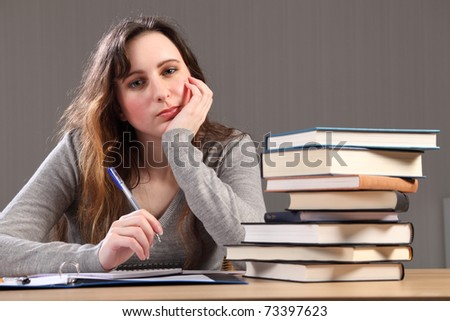 Young caucasian student girl at home looking tired, sitting to her desk studying with work books stacked up alongside her. - stock photo