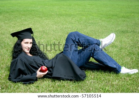 Young caucasian student laying on the grass