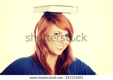 Young caucasian student with book on her head