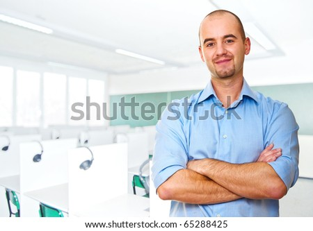 young caucasian teacher and classroom background - stock photo