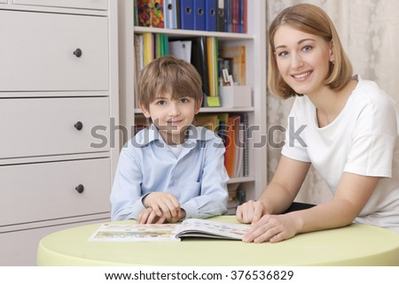 Young caucasian teacher and the pupil. Sit at the green table. Read the textbook. The show on the page. They smile - stock photo