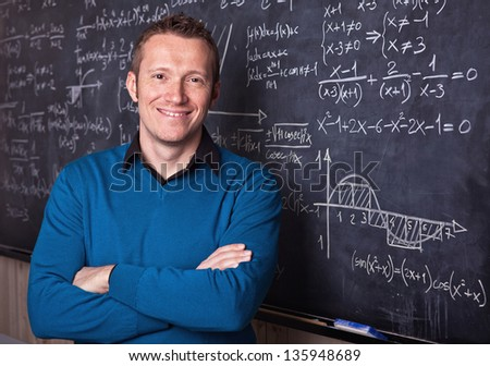 young caucasian teacher portrait with blackboard background - stock photo