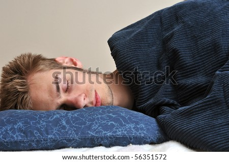 Young Caucasian teenage adult male sleeping on his pillow with his eyes closed. - stock photo