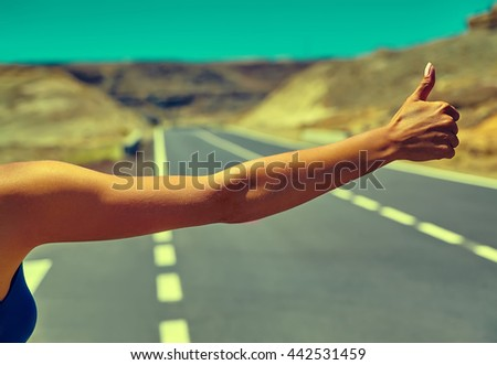 Young caucasian tourist hitchhiking along a road in sunset