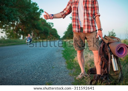 Young caucasian tourist with backpack hitchhiking along a road in sunset - stock photo
