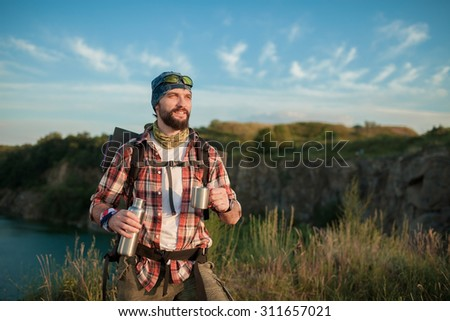 Young caucasian tourist with backpack resting and drinking water on the top of hill - stock photo