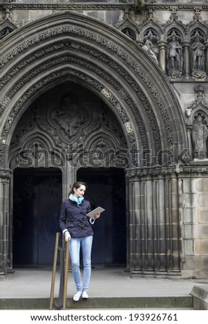 Young caucasian tourist with her tablet standing near a Cathedral in Edinburgh, Britain. - stock photo
