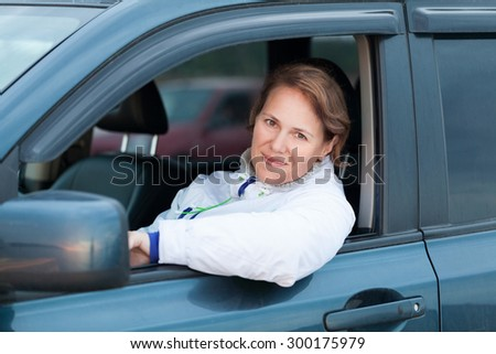 Young Caucasian woman as a driver, outdoor portrait in open car window - stock photo