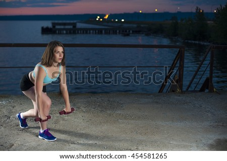 Young caucasian woman doing lunges with dumbbells on sea pier. fitness workout outdoors.  - stock photo