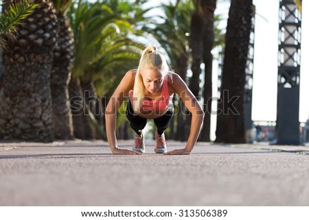 Young caucasian woman doing press ups in tropic urban setting with palm trees, athletic female runner with beautiful figure dressed in workout gear doing push-ups outdoors before begin her morning run - stock photo