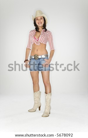 Young Caucasian woman dressed as cowgirl looking at viewer. - stock photo