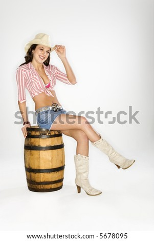 Young Caucasian woman dressed as cowgirl sitting on a barrel and tilting hat at viewer. - stock photo