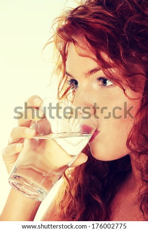 Young caucasian woman drinking water from glass - stock photo