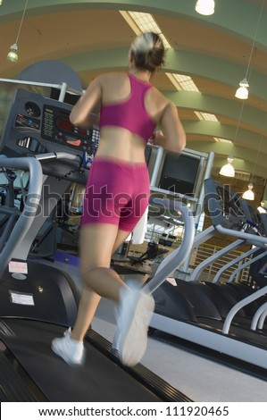 Young caucasian woman exercising on treadmill - stock photo