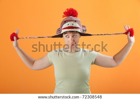 Young Caucasian woman fiddles with her sock monkey cap - stock photo