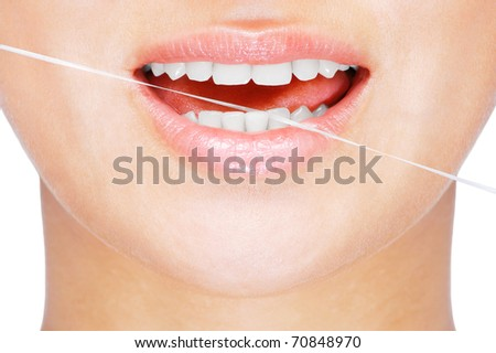 Young caucasian woman flossing her teeth , close up , white background - stock photo