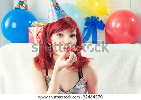 Young caucasian woman fooling about with party horn blower - stock photo