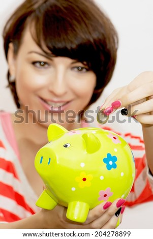 Young caucasian woman gives a euro coin into decorative ceramic piggy bank. - stock photo