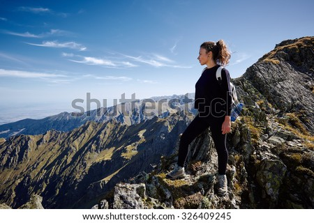 Young caucasian woman hiker on a rocky mountain trail - stock photo