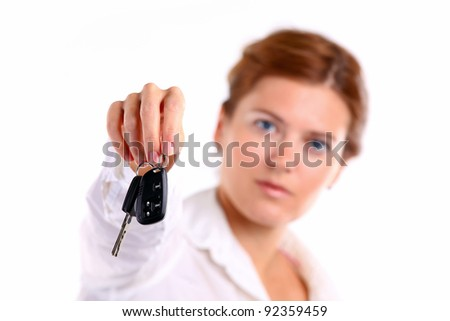 Young caucasian woman holding car key. Image with shallow depth of field. The key is in focus.