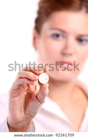 Young caucasian woman holding one euro coin. Image with shallow depth of field. The coin is in focus. - stock photo