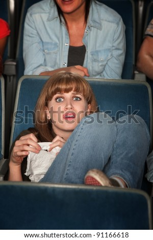 Young Caucasian woman holding tissue weeps in theater - stock photo
